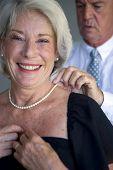 Homem fechando um colar de mulher