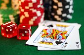 foto of crap  - stacks of gambling chips playing cards and dice on green background - JPG