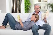 Senior couple relaxed reading a book