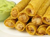 picture of flauta  - A plate of chicken taquitos with a side of guacamole - JPG
