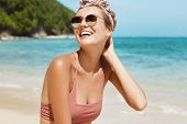Positive Pleased Female Model Spends Summer Holidays On Exotic Tropical Sea Shore With Cliff Behind, poster