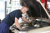 Retrato de um mecânico sorridente, trabalhando em um carro na garagem