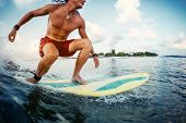 Young man surfer rides the ocean tropical wave during sunrise surf session poster