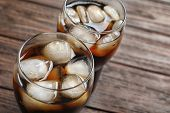 Two glasses of refreshing cola with ice on wooden table, closeup poster