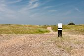 Dutch coast with dunes and a wooden distance marker