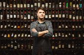 Barkeeper In Apron Stands In Wine Cellar With Large Shelves Full Of Closed Bottles With Exquisite Al poster