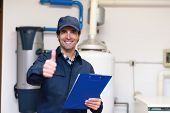 Smiling technician servicing a hot-water heater poster