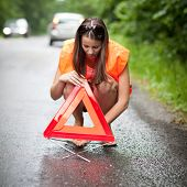 Young female driver wearing a high visibility vest/safety vest, putting in place the warning triangl