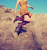 pretty woman in a skirt jumping up in cowboy boots in a wheat field on a hot summer day toned with a poster
