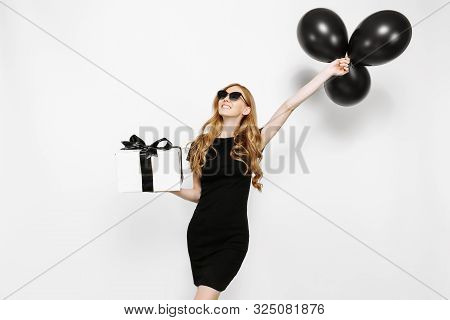 poster of Happy Elegant Young Girl In Black Dress Happily Holding Gift With Black Friday Ribbon And Black Ball