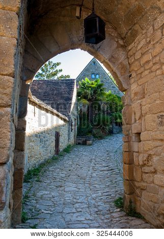 poster of Typical French Townscape With Ancient Housest And Cobblestone Street In The Traditional Town Beynac-