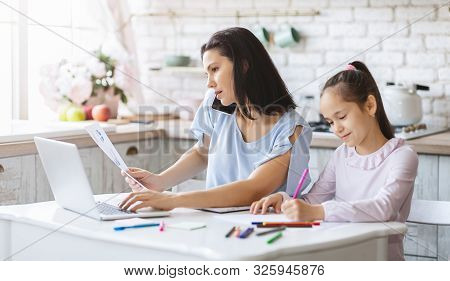 poster of Busy Family. Mother Working From Home While Daughter Doing Her Homework In Kitchen, Panorama