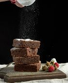 Stack Of Square Baked Brownie Chocolate Cake Slices Sprinkled With White Sugar From An Iron Sieve, S poster