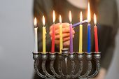 Jewish Woman Lighting Hanukkah Candles In A Menorah. People Celebrate Chanukah By Lighting Candles O poster