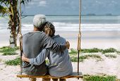 Asian Senior Couple Or Elderly People Walking And Siting At The Beach On Their Weekend Vacation Holi poster