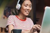 Portrait of charming asian woman listening to music with headphones while using laptop computer in c poster