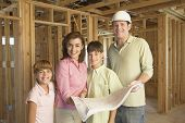 stock photo of nuclear family  - Family with blueprints on construction site - JPG