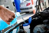 closeup of a young caucasian man pouring windshield washer fluid into the windshield washer fluid ta poster