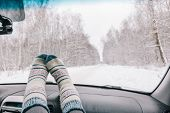 Woman feet in warm woolen socks on car dashboard over snow view. Having weekend trip in winter fores poster