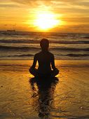 Young Woman Sitting On The Beach, Silhouette At Sunset. Young Woman Practicing Yoga Outdoors. Harmon poster