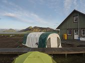 Colorful Tents And Green Tourist Hut At Alftavatn Camping Site With Blue Lake And Green Hills And Gl poster