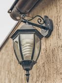 A Photo Of A Vintage Street Lamp Mounted On The Wall Of A House With Sepia Effect.application In The poster