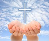 Hands holding Christian cross with light beams