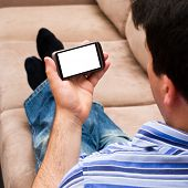 A man relaxing on the couch and looks at a smartphone