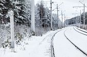 Empty Electric Mainline Railway In Winter Woods With Distance Mark