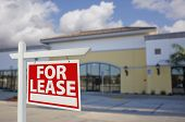 Vacant Retail Building with For Lease Real Estate Sign in Front.