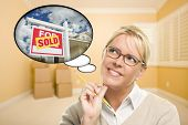 Attractive Woman in Empty Room with Thought Bubble of a Sold For Sale Real Estate Sign in Front of H