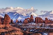 stock photo of turret arch  - Turret Arch with Snow Mountains at sunset - JPG