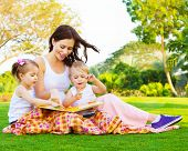 Picture of beautiful woman with daughter and son sitting down on green grass field and read fairytal