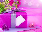 Photo of beautiful romantic still life, pink giftbox with violet silk ribbon, fresh flowers bouquet,