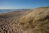 foto of anglesey  - Rhosneigr beach with a sand dune and an empty beach with the village in the distance Wales coast path Anglesey Wales UK - JPG