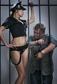 image of male-domination  - sexy lady police officer guards the offender in prison - JPG
