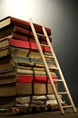 Old books and wooden ladder, on grey background