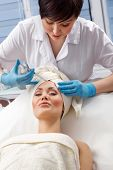 image of lip augmentation  - Young woman receiving a botox injection in her  forehead - JPG
