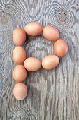 Una letra P de los huevos de Pascua. En una textura de madera.