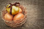 Easter Eggs With Brown Ribbon In A Nest On A Wooden Texture.