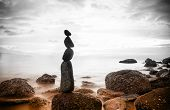Nature background. Sea dramatic landscape, harmony environment and zen stones tower silhouette. Medi