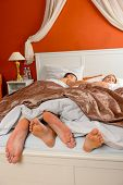 Sleeping couple barefoot lying bed room side by side