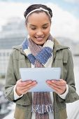 Smiling woman using tablet while standing outside
