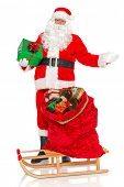 Santa Claus or Father Christmas with a sack full of gift wrapped toys and presents on a sled, isolat