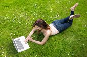 Pretty young woman lying on a lawn using her laptop on a sunny day