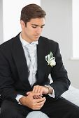 Young bridegroom watching the clock wearing a suit