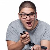 foto of dork  - A fun loving video gamer playing with a wireless joystick over a white background - JPG