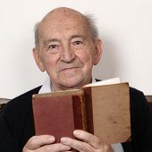 stock photo of grandpa  - Portrait of a grandpa reading fairy tales from an old book - JPG