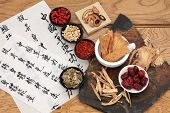 Traditional chinese herbal medicine selection with mandarin calligraphy on rice paper over oak. Translation describes the medicinal functions to maintain body and spirit health and balance energy.
