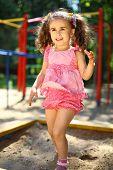 Little girl jumping into a sandbox
